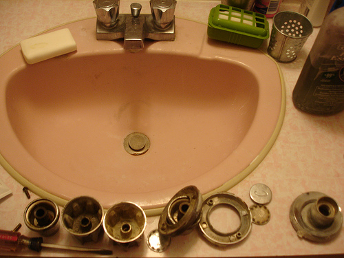 Pink lavatory basin and disassembled pieces of faucet and drain